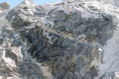 Photo 2014-196: Strongly foliated (SP1-2) sericite schist deformed by SW verging FP4 folds (mine-scale nomenclature; Pit A, West wall).